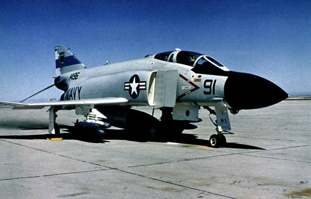 A view of a parked Navy F-4C Phantom II aircraft, armed with practice bombs. The aircraft is being used for the testing of the Global Positioning System satellite