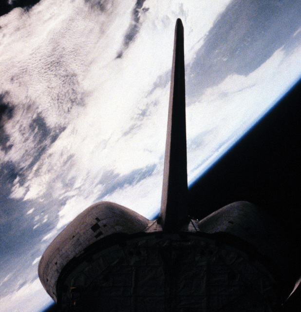 A view of the tail section and part of the cargo bay of the Columbia space shuttle orbiter in orbit, with the Earth in the background