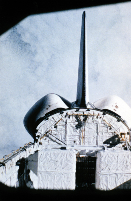 A view of the tail section and part of the cargo bay of the Columbia space shuttle orbiter while in orbit, with the cloud-covered Earth in the background