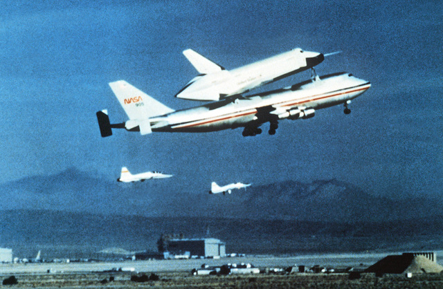 Right side view of the 747 Shuttle carrier aircraft carrying the Enterprise Space Shuttle Orbiter during take-off. The aircraft is flanked by two F-5 Tiger II aircraft