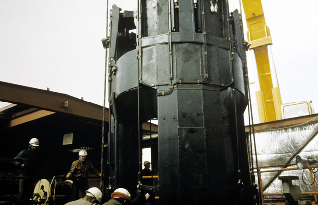 Technicians, using a forklift, prepare to move a piece of a Minuteman laser-guided missile 30