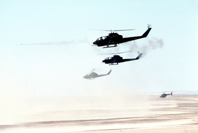 A left side view of three AH-1G Cobra gunship helicopters and an OH-58 Kiowa helicopter in flight as a combined armament live fire exercise takes place during BRIGHT STAR '82. BRIGHT STAR involves troops from the US, Egypt, Sudan, Somalia and Oman