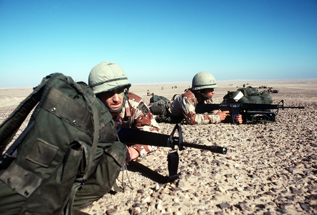Members of the 82nd Airborne Division, armed with M-16A1 rifles, take defensive positions in the Sahara Desert during exercise Bright Star '82
