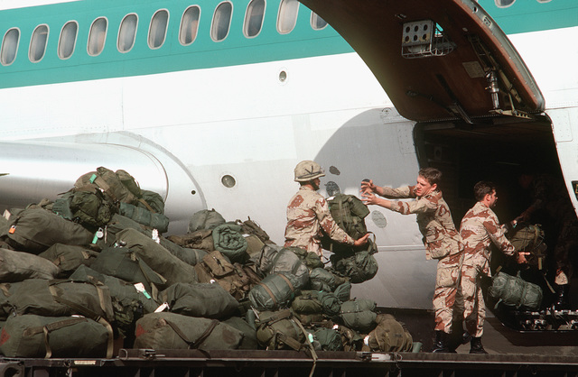 Members of the 82nd Airborne Division offload equipment from a chartered Transamerica DC-10 aircraft upon their arrival to participate in Exercise BRIGHT STAR '82