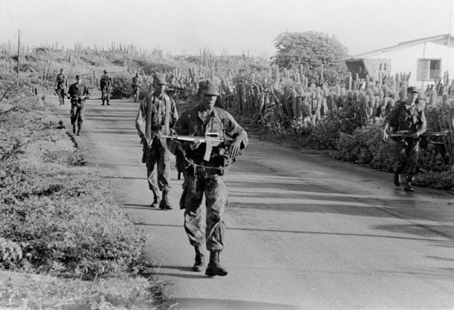 U.S. Marines of Co. K, 3rd Bn., 6th Marines, are on patrol as they walk down a village street. The Marines are carrying their standard M-16A1 rifles as they participate in Operation Unitas XXII