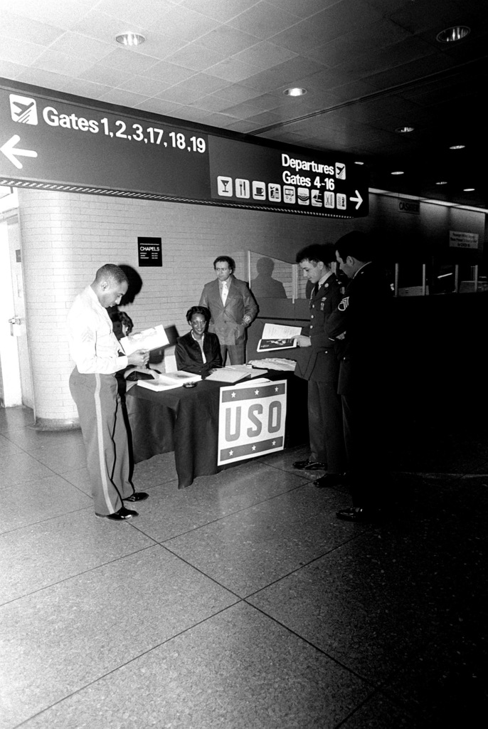 Marine SGT Ron Bethune of the 1ST Marine Corps District recruiting office and two Army sergeants look over pamphlets they will be handing out here at the John F. Kennedy Airport. They are standing in front of the new USO booth