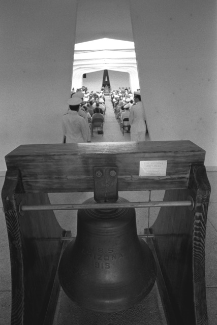 A view of one of the two bells used on the battleship USS ARIZONA (BB-39). The bell has been placed at the entrance to the USS ARIZONA Memorial. In the background, a ceremony commemorating the 40th anniversary of the Japanese attack on Pearl Harbor is taking place