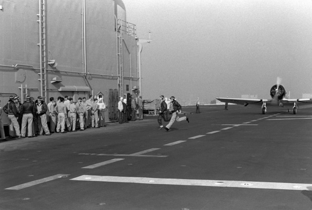 "Actors run from a vintage T-6 trainer aircraft being used to simulate a dive bomber during the filming of the movie ""Winds of War"" aboard the amphibious assault ship USS PELELIU (LHA 5). Several crewmen from the ship were used as ""extras"" in the Paramount Studios film"