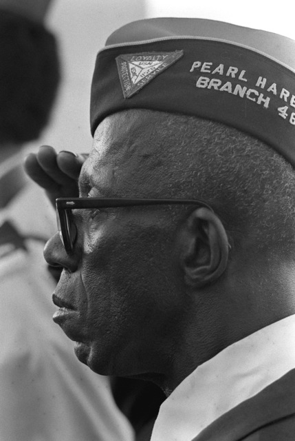 Byron Devonish, a guest at the Pearl Harbor Day ceremony commemorating the 40th anniversary of the attack on Pearl Harbor, salutes as the flag is raised during morning colors aboard the USS ARIZONA Memorial