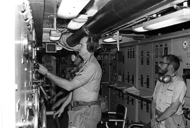 CHIEF Electrician's Mate (EMC) Robert Gordon, left, EM3 Kenneth Jackson, center, and EM2 Rual Aquino, right, operate equipment in the main control room aboard the salvage ship USS OPPORTUNE (ARS 41) during a general quarters drill on the 40th anniversary of the attack on Pearl Harbor