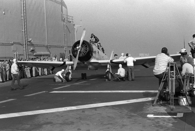 "Crewmen from the amphibious assault ship USS PELELIU (LHA 5) place chocks against the wheels of a T-6 trainer aircraft being used to simulate a World War II dive bomber for the Paramount Studios film ""Winds of War"""