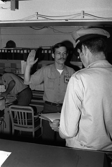 Electrician's Mate 1ST Class (EM1) W. Loveless is given the re-enlistment oath by Commander C. Burch aboard the amphibious assault ship USS TARAWA (LHA 1) on the 40th anniversary of the attack on Pearl Harbor