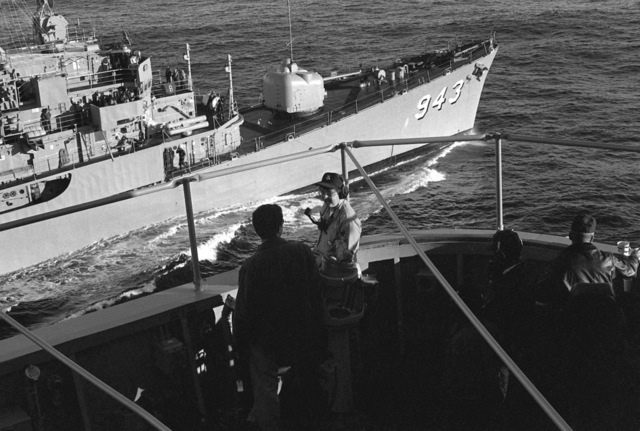 Lieutenant Donahue, left, and Navy Counselor 1ST Class (NC1) Moore discuss the underway replenishment operation as the destroyer USS BLANDY (DD 943) moves into position alongside the ammunition ship USS SANTA BARBARA (AE 28). The photograph was taken on the 40th anniversary of the attack on Pearl Harbor