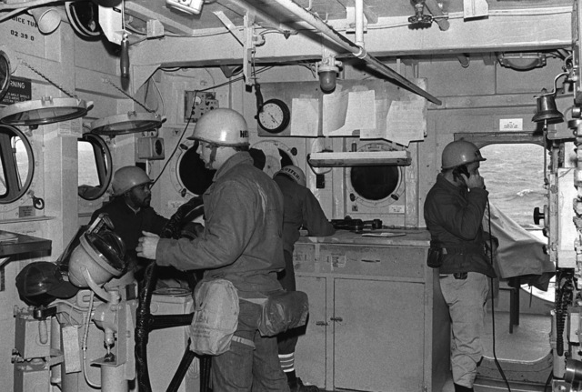 Ship's Serviceman 2nd Class (SH2) Joe Green, Boatswain's Mate SEAMAN (BMSN) Robert Watkins and Lieutenant Michael O'Moore, in the pilothouse, take part in a general quarters drill aboard the salvage ship USS OPPORTUNE (ARS 41). The photo was taken on the 40th anniversary of the attack on Pearl Harbor