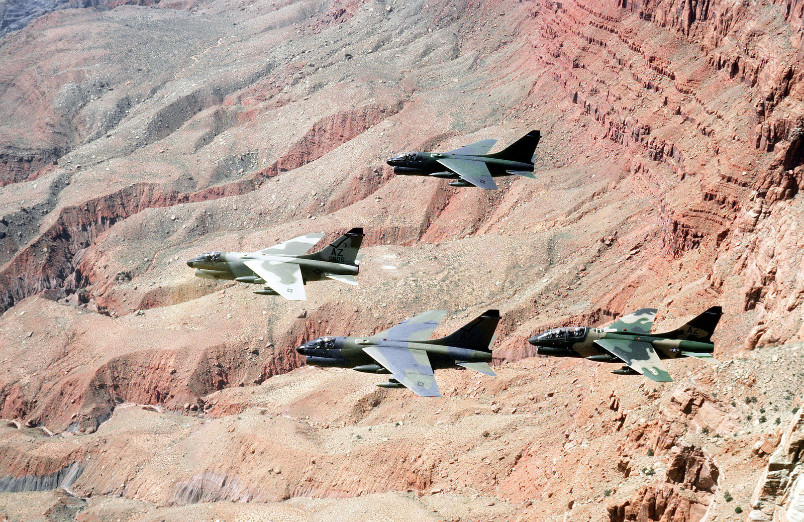 Three A-7D Corsair II aircraft and one A7K Corsair II aircraft, at the far right, fly in formation over the desert. The aircraft, each in a different paint scheme, are being tested against desert and forest background for visibility