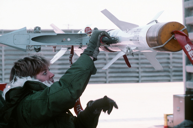 A missile is hooked up to the wing of an F-16 Fighting Falcon aircraft during a practice load and preflight exercise