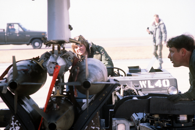 Ground crewmen line up a bomb loader to an F-16 Fighting Falcon aircraft during a practice load and preflight exercise