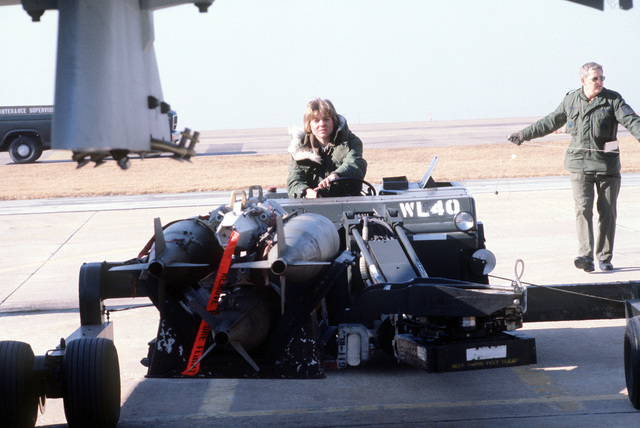 Ground crewmen move a bomb loader toward an F-16 Fighting Falcon aircraft during a practice load and preflight exercise