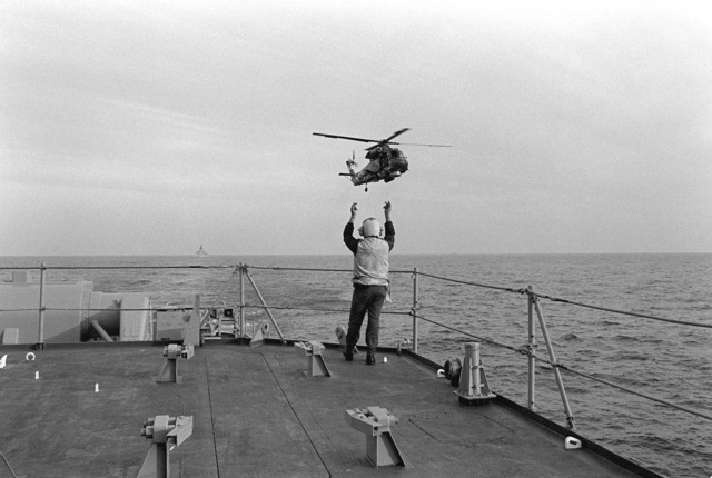 The landing signal enlisted petty officer signals to an SH-2F Seasprite helicopter from Light Helicopter Antisubmarine Squadron 34 (HSL-34) preparing to land aboard the guided missile destroyer USS COONTZ (DDG-40)