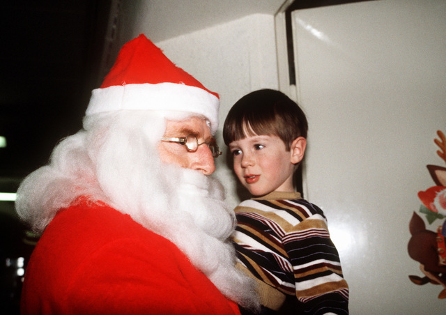 """CMSGT of the Air Force A. L. """"Bud"""" Andrews, dressed as Santa Claus, listens to four-year-old Brian J. Hatlelid tell him what he wants for Christmas. Brian's father, Joseph M., is a captain and pilot with the 37th Tactical Airlift Squadron at Rhein-Main Air Base"""