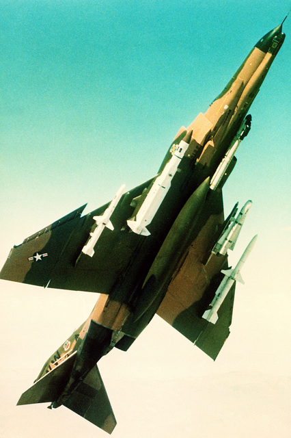 An air-to-air view of the underside of an F-4G Phantom II aircraft carrying an AGM-45 Shrike air-to-ground tactical missile; an AGM-65 Maverick air-to-ground, TV-guided tactical missile; and AGM-78 Standard Arm training missile; and an AGM-88 Harm anti-radiation, high velocity, air-launched guided missile
