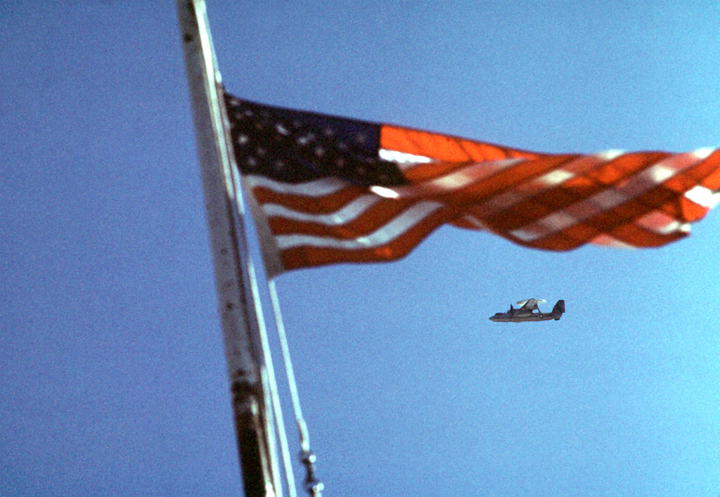 An air-to-air left underside view of an E2-C Hawkeye aircraft near the U.S. flag in the tower area