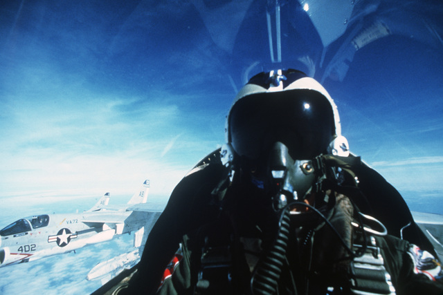 A close-up view of a pilot in the cockpit of an A-7E Corsair II aircraft while flying in formation with other A-7Es of Attack Squadron 72 (VA-72)