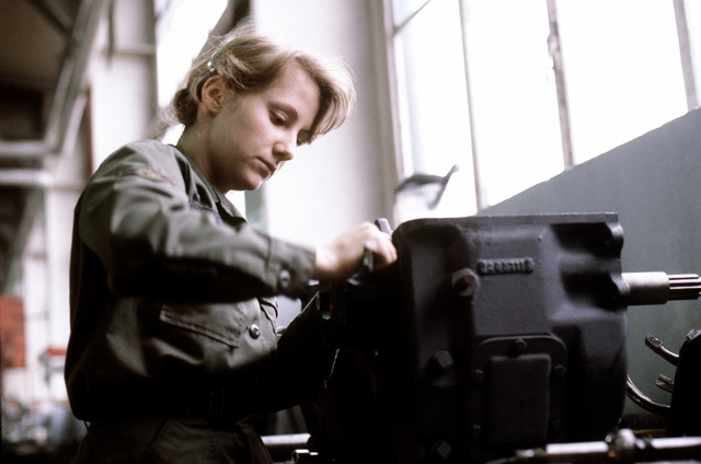 A female airman works on a piece of equipment