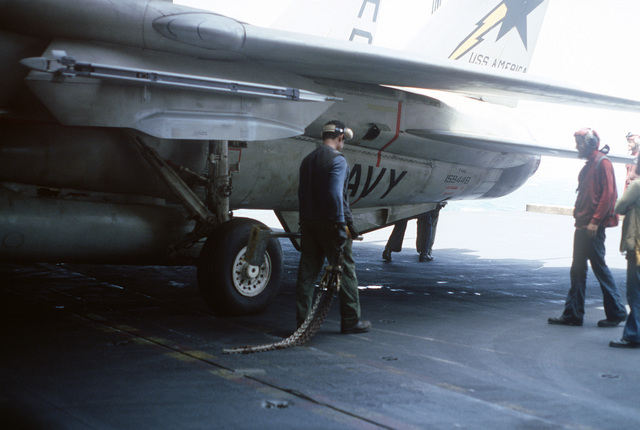 A flight deck crewman removes tie-down chains from an F-14A Tomcat aircraft aboard the aircraft carrier USS AMERICA (CV 66)