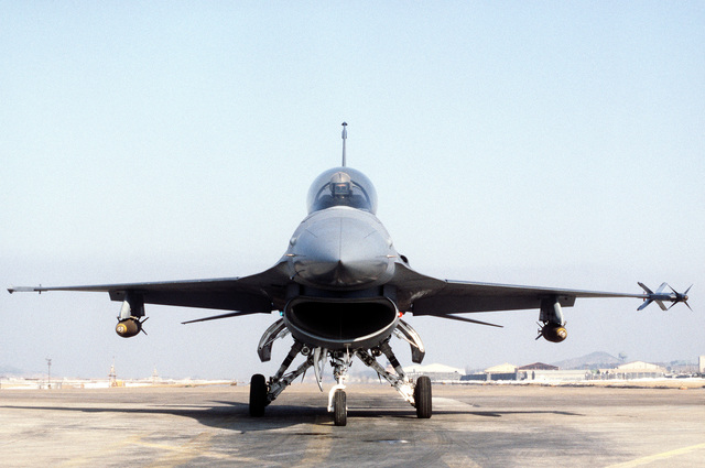 A front view of an F-16 Fighting Falcon aircraft armed with an AIM-9L Sidewinder training missile on the wingtip and two Mark 84 2,000-pound live bombs