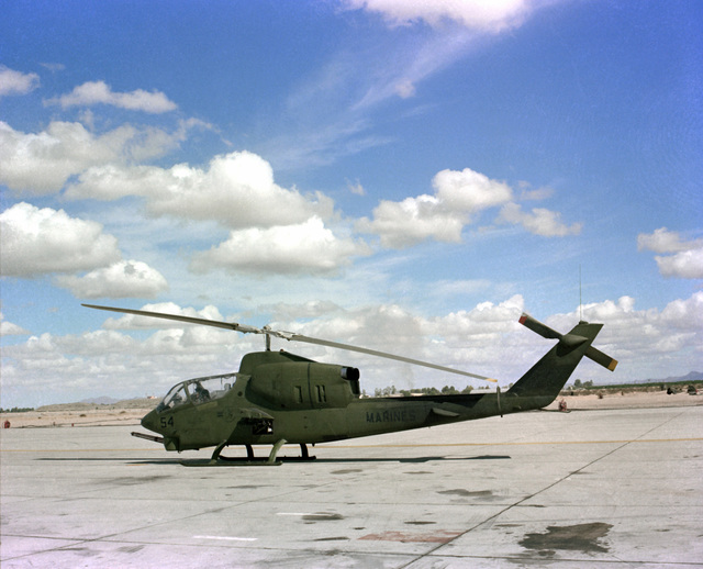 A left side view of a Marine AH-1 Cobra helicopter parked on the flight line at Naval Air Station, Whiting Field
