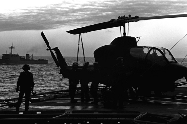 A Marine AH-1 Sea Cobra helicopter from Marine Light Helicopter Squadron 167 (HML-167) is loaded aboard the amphibious assault ship USS GUAM (LPH-9) for the trip to Norway. The Cobra will be used in support of the 1ST Battalion, 6th Marines, cold weather training