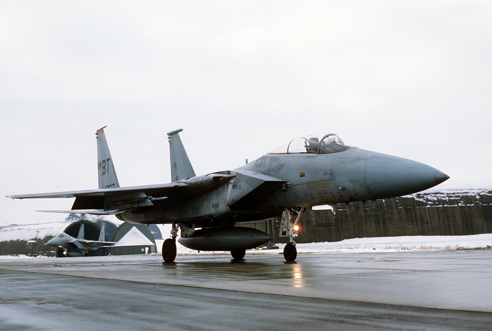 A right front view of an F-15 Eagle aircraft taxiing on the flight line. The aircraft is carrying a centerline auxiliary fuel tank