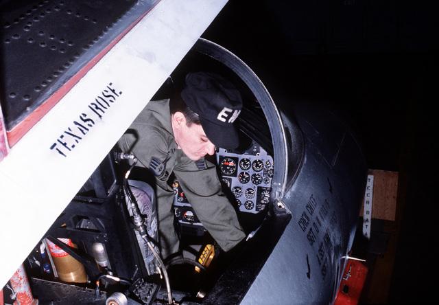 A staff sergeant preflight checks an F-15 Eagle aircraft cockpit