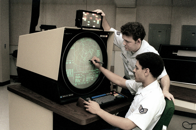A staff sergeant watches as his instructor monitors a radar scope and checks a missile course on the screen at the PAVE PAWS radar site. The PAVE PAWS provides detection of enemy missile launches and keeps track of objects in space