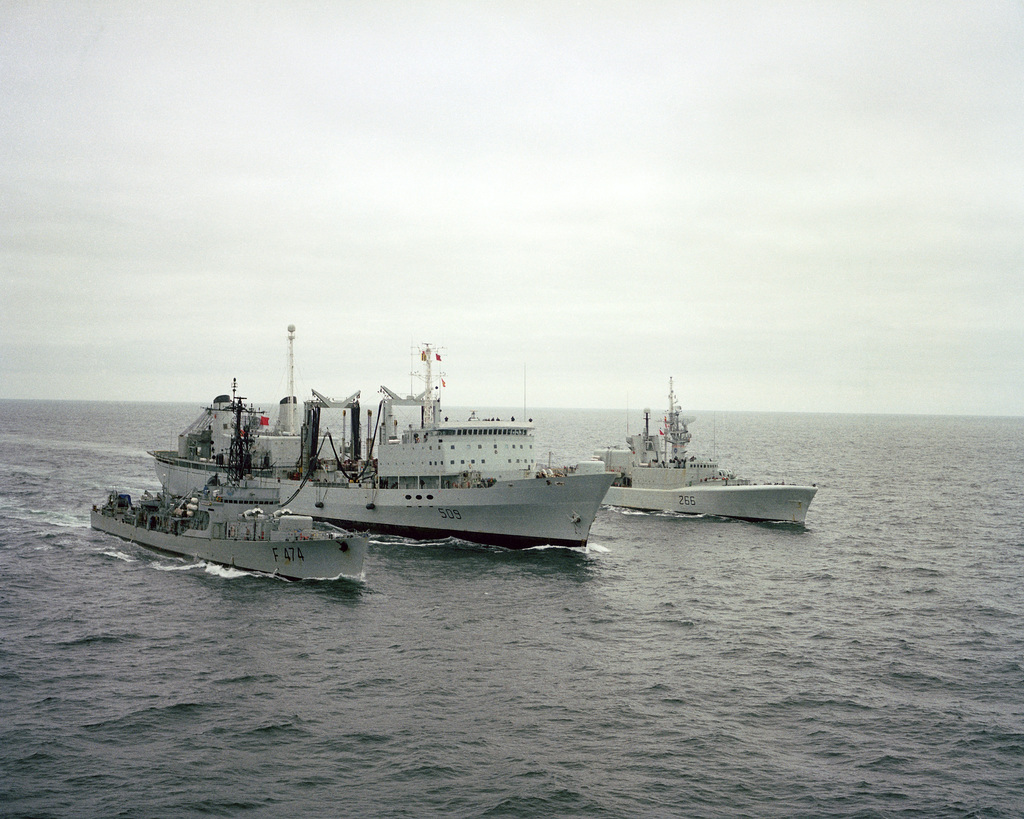 A starboard bow view of the Canadian replenishment ship HMCS PROTECTEUR (AOR 509) refueling the Canadian frigate HMCS NIPIGON (266) off its port side and the Portugese NRP ALMIRANTE MAGALHAES CORREA (F 474) off its starboard side