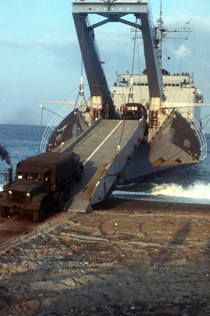 A U.S. Marine truck is unloaded from the tank landing ship USS NEWPORT (LST-1179) during Valiant Blitz, the amphibious assault landing phase of exercise Team Spirit '82