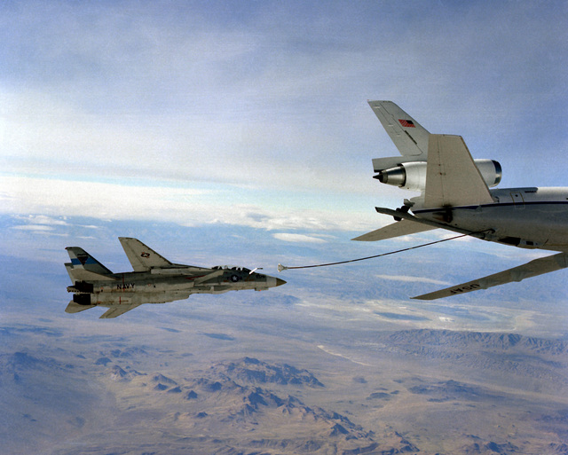 Air-to-air right side view of an F-14 Tomcat aircraft as it moves into position to be refueled through the boom of a KC-10A Extender aircraft