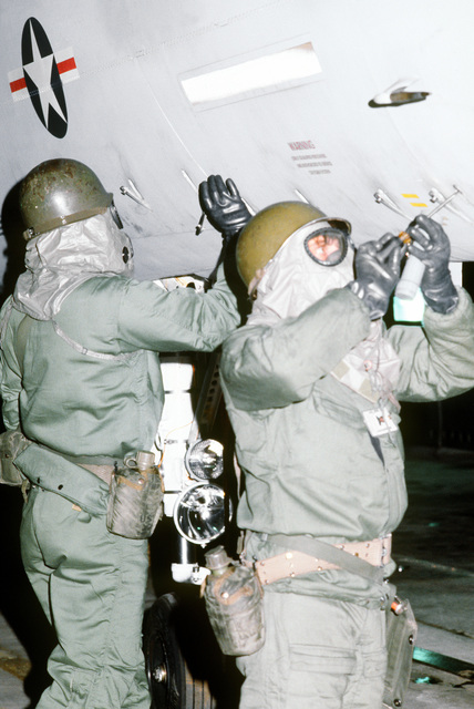 Airmen in protective chemical warfare gear perform preflight maintenance on an F-15 Eagle fighter aircraft