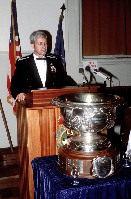 An Air Force colonel speaks before a crowd during an award ceremony. The Hughes Aircraft Co. Achievement Trophy stands before the platform