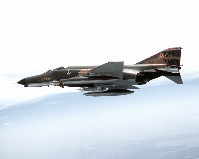 AN air-to-air left side view of an F-4E Phantom II aircraft over Nellis Air Force Base. AN auxiliary fuel tank is carried on each wing. A Mark 84 bomb is loaded on the left wing and two AIM-9J Sidewinder missiles are on the right. The aircraft is assigned to the 347th Tactical Fighter Wing