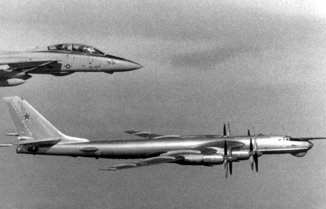An air-to-air right side view of a Soviet Tu-95 Tupolev aircraft and a U.S. Navy F-14A Tomcat aircraft, top. The F-14A is from Fighter Squadron 211 (VF-211) embarked aboard the aircraft carrier USS CONSTELLATION (CV-64). The NATO designation of the Tu-95 is Bear