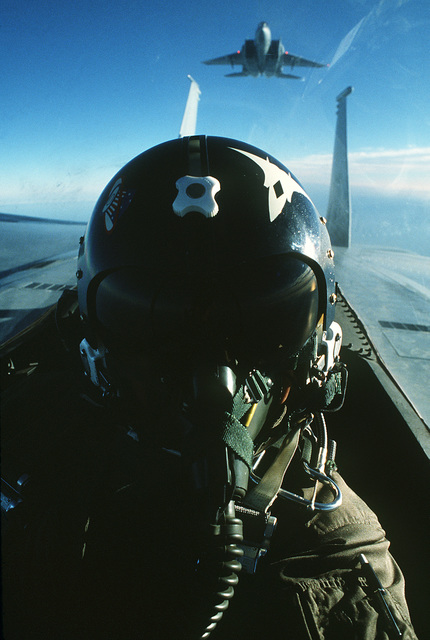 AN air-to-air view of a pilot in the cockpit of an F-15 Eagle aircraft. Another F-15 is in the background