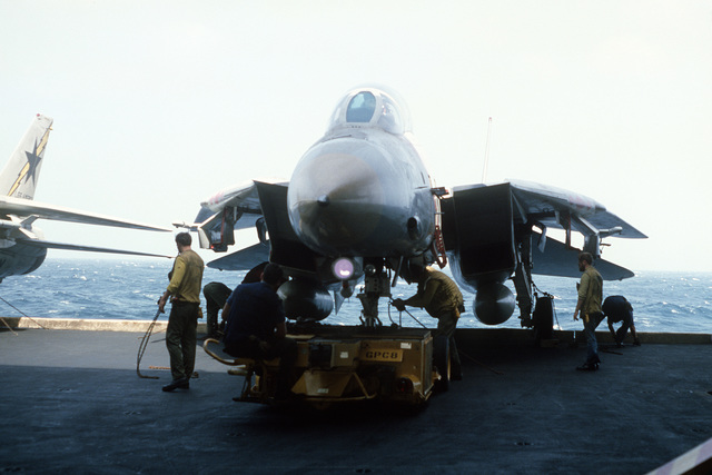 An F-14A Tomcat aircraft is transported on the elevator of the aircraft carrier USS AMERICA (CV 66)