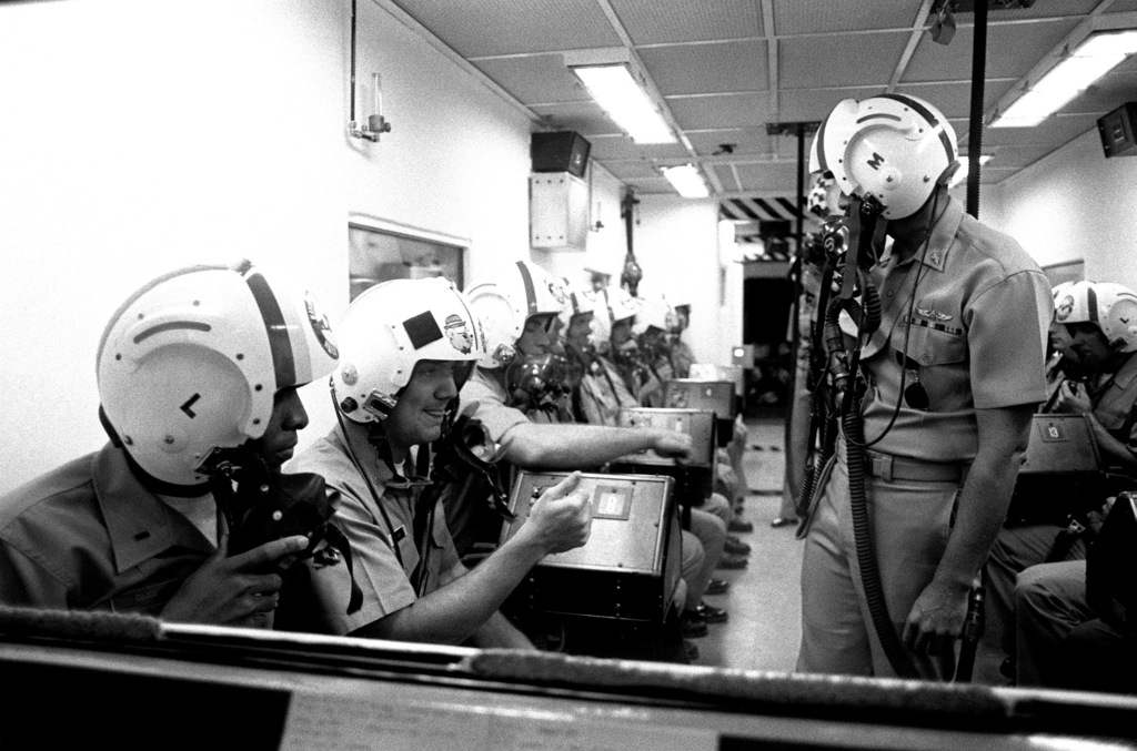 An officer watches as a class of candidates goes through a pressure chamber exercise at Aviation Officer Candidate School