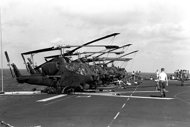 Eight Marine AH-1 Sea Cobra helicopters and UH-1N Iroquois helicopters are tied down on the flight deck of the amphibious assault ship USS GUAM (LPH-9). The helicopters will be used in support of the 1ST Battalion, 6th Marines, cold weather training