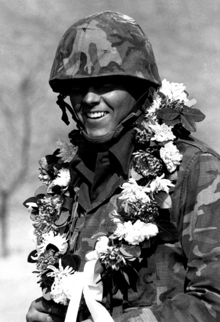 Marine Corps LCPL Stephen Dickerson, India Company, displays a flower garland, presented to him in a parade, during exercise Team Spirit '82