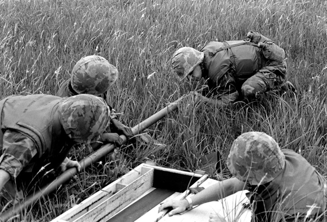 Marines of the 3rd Combat Engineer Battalion undergo training with the bangalore torpedo. PFC Eric Hamby slides two sections together prior to positioning the torpedo under a barb wire fence