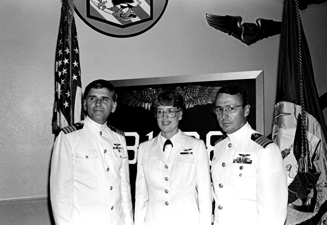 Retired CAPT James R. Boling, USNR, and CAPT Floyd W. Carter, commander, Naval Air Training Unit, Mather Air Force Base, pose with ENS Mary A. Crawford following her June 1981 graduation from Interservice Undergraduate Navigator Training (IUNT). Crawford, whose first assignment is to Antarctic Development Squadron 6 (VXE-6), is the U.S. Navy's first woman naval flight officer (NFO)