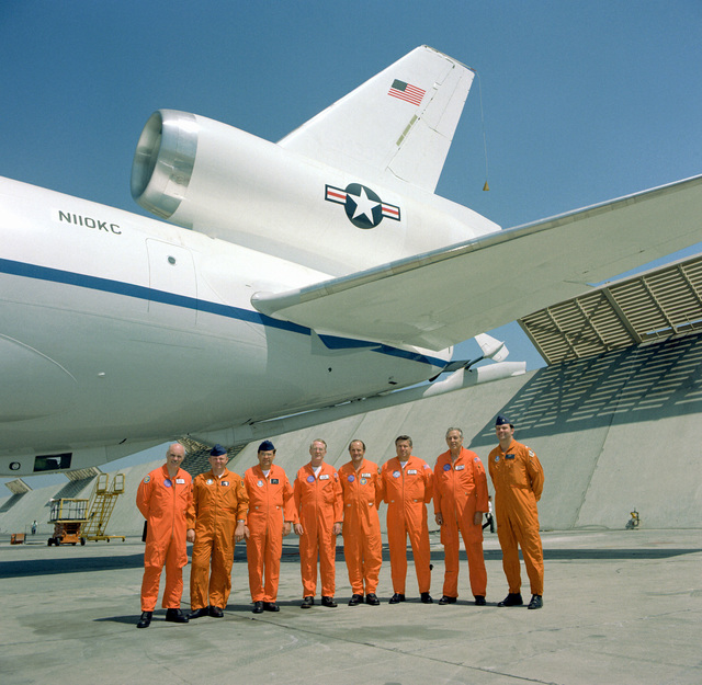 The first flight crew of a KC-10A Extender aircraft standing under the left wing of the aircraft
